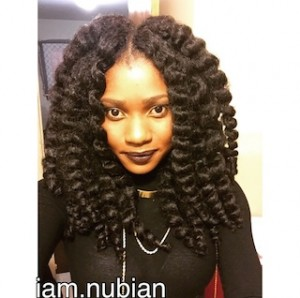 Woman wearing crochet braids in black outfit and dark lipstick