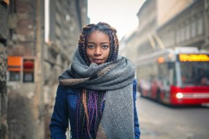 Black woman with braids in winter wearing a protective hairstyle