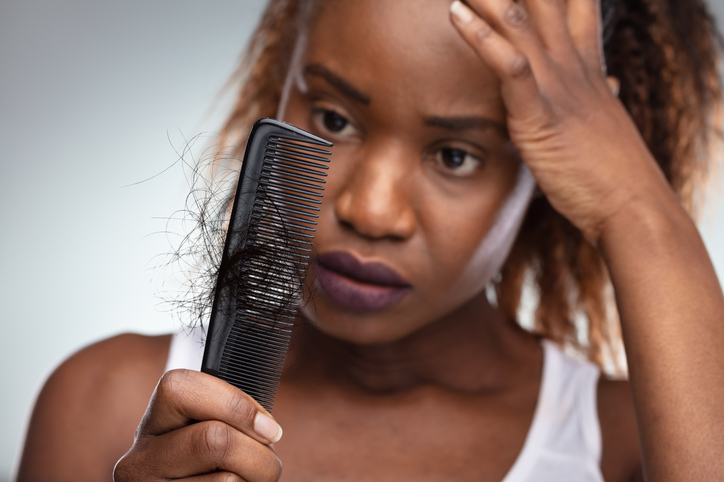 A black woman looking at hair in her comb.
