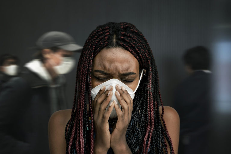Woman coughing into his mask