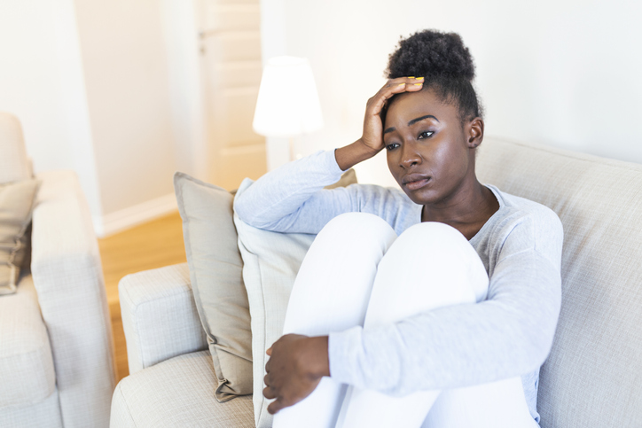 Black woman sitting on couch frustrated about her thinning edges