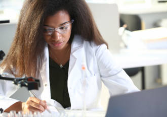 Black female chemist looking at paper