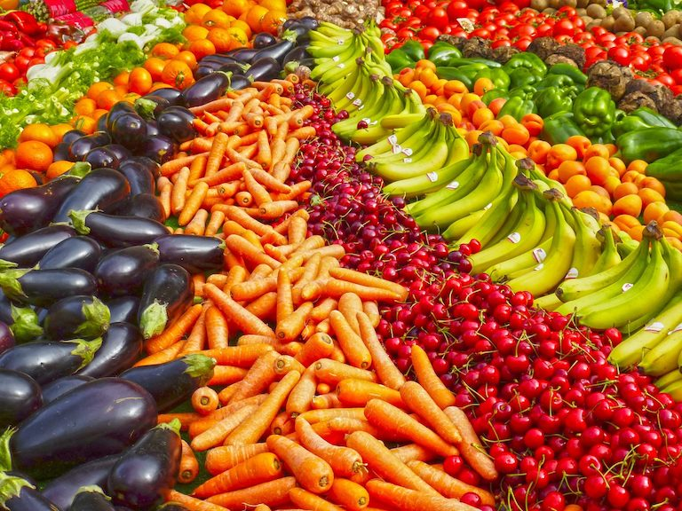 Photo of an array of fruits and vegetables that are full of micronutrients needed for hair growth, such as bananas, carrots, eggplants, tomatoes, cherries, peppers, oranges, broccoli
