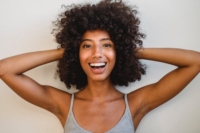 Black woman with healthy hair and putting her hands on her head while smiling with a big, bright and beautiful smile.