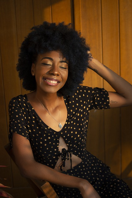 Black woman with afro smiling with her eyes closed