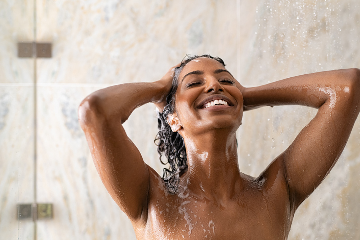 Black woman washing hair in shower